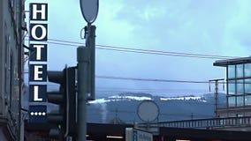 Hotel sign in city street, snowy mountain ridge on horizon, popular ski resort stock video
