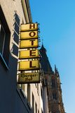 Hotel sign with the historic town hall in background in the old town of Cologne, Germany. Cologne, Germany - February 24, 2018: Hotel sign with the historic town Royalty Free Stock Photos