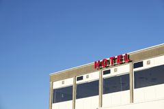 Hotel sign red letters and summer blue sky accommodation for tourists on holiday in exotic location. Hot stock photography