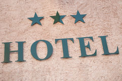 Hotel signage with three stars on stoned wall. Closeup of hotel signage with three stars on stoned wall Stock Image