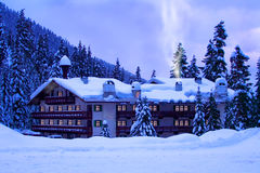 Hotel in snow. A hotel located in mountains covered by deep snow. Glow of windows and smoke give warm and cozy holiday feeling Stock Photo