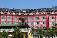 Hotel with solar roof. Large pink hotel with solar panels across the roof Royalty Free Stock Photo