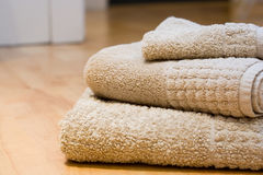 Hotel style towels. Towels on a laminate wooden floor Stock Image
