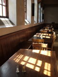 Hotel: sunny old dining room. Old dining room of historic hotel with sunlit wooden tables and chairs Stock Image