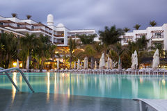 Hotel with swimming pool at dusk Royalty Free Stock Photography