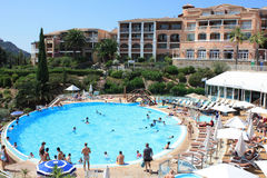 Hotel with swimming pool at French Riviera. People getting tanned and swimming in the pool at hotel royalty free stock image