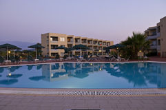 Hotel and swimming pool. A Greek hotel with a swimming pool in the foreground. There are some sunshades and sunchairs around the pool. The hotel building has Royalty Free Stock Image