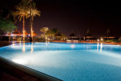 Hotel swimming pool at night. Large swimming pool in a luxury tropical hotel lit up at night Stock Photo