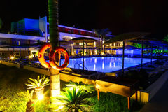 Hotel with swimming pool and palm at night life preserver in foreground Royalty Free Stock Images