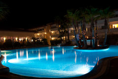 Hotel swimming pool and palms at night Stock Photos