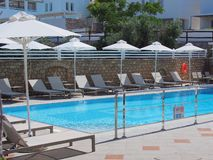 Hotel Swimming Pool. Sun beds and umbrellas around blue water hotel swimming pool Stock Photo