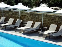 Hotel Swimming Pool, Sun Beds and Umbrellas. A blue water hotel swimming pool, with white sun bed recliners lounges and white umbrellas Royalty Free Stock Photography