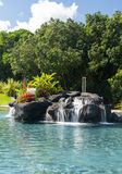 Hotel swimming pool with waterfall royalty free stock photography