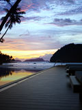 Hotel terrace with borderless swimming pool. In front of beautiful tropical sunset stock photography