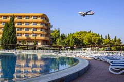 A hotel for tourists, a swimming pool with sun beds and an airplane flying over them in the early summer morning. Croatia, Europe stock image