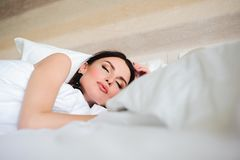 Hotel, travel and happiness concept - beautiful woman sleeping in bed. royalty free stock photography