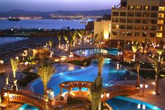 Hotel at twilight. The luxurious Aqaba Jordan Hotel at twilight, illuminated swimming pools and lavish interior yard with city in the distance. Located on royalty free stock photos