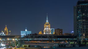 Hotel Ukraine and pedastrian bridge timelapse, landmark near historic center of Moscow. Cityscape in snowy winter. Evening. Panorama view on city at night stock footage