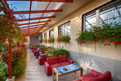 Hotel veranda. With tiled floor, flower pots, creepers and  red settees and coffee tables Royalty Free Stock Photos