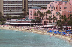 Hotel on Waikiki beach. Scenic view of tourists on Waikiki beach with pink hotel in background, Honolulu, Hawaii Stock Images
