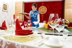 A hotel waiter before table arrangement of tablewa stock image