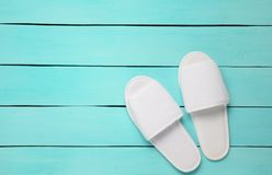 Hotel white slippers on a blue wooden floor. Top view.  Royalty Free Stock Photo