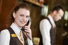 Hotel worker with phone on reception Royalty Free Stock Image