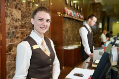 Hotel worker on reception. Happy female receptionist worker standing at hotel counter Stock Photos