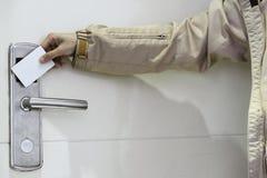 Hoteldeur - woman& x27; s hand die een magnetische zeer belangrijke kaart van het streephotel voor het elektronische slot van de  royalty-vrije stock afbeeldingen