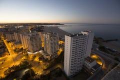 Hotell och strand på banken av havet under soluppgång Fotografering för Bildbyråer