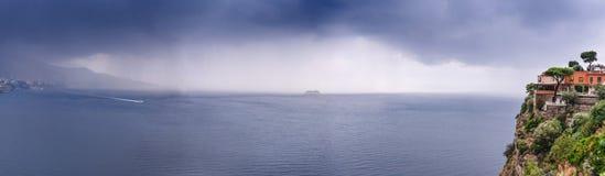 Hotell p? kanten av berget, med en sikt till havsregnmolnen ?ver h?rliga Sorrento, Metafj?rd i Italien, lopp och royaltyfri bild