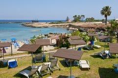 Hotell sätter på land med turkosvatten av medelhavet med fartyget och träd Arkivbilder