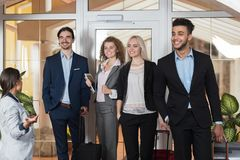 Hotelladministratören Welcome Business People i lobbyen, gäster för grupp för blandningloppBusinesspeople ankommer Royaltyfri Fotografi