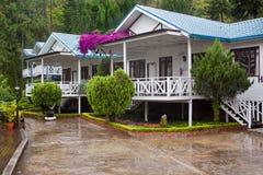 Hotellandhäuser unter Regen Stockbild