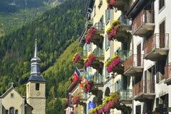 Hotellfasad och kyrkan bakom i staden Chamonix Arkivbilder
