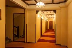 Hotellhall för gammal stil med träbruna dörrar, rödaktig matta, Arkivbilder