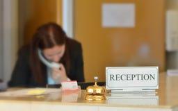 Hotellmottagandeskrivbord med klockan Arkivfoton