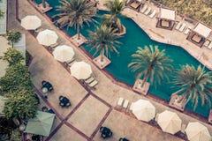 Hotellpoolsiden med slags solskydd och gömma i handflatan Arkivfoto
