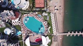 Hotellpoolsiden med slags solskydd och gömma i handflatan gem Top beskådar skjutit Att omge för simbassäng gömma i handflatan och stock video