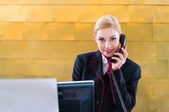 Hotellreceptionist med telefonen på det främre skrivbordet Royaltyfri Foto