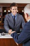 Hotellreceptionist som ger det nyckel- kortet till pensionären Royaltyfri Fotografi