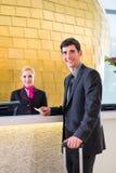 Hotellreceptionisten kontrollerar in mannen som ger det nyckel- kortet arkivbilder