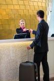 Hotellreceptionisten kontrollerar in mannen som ger det nyckel- kortet Arkivfoto