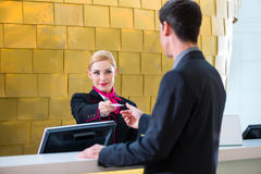 Hotellreceptionisten kontrollerar in mannen som ger det nyckel- kortet royaltyfria bilder