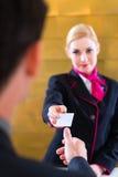 Hotellreceptionisten kontrollerar in mannen som ger det nyckel- kortet Royaltyfri Bild