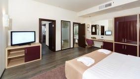 Hotellrum med en stor säng, en TV och någon hyr rum Royaltyfri Fotografi