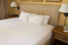Hotellsemesterortsäng och vitlinne royaltyfri bild