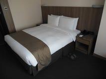 Hotellsovrum med rena säng-, nattduksbord-, vit- och bruntfärger royaltyfria foton