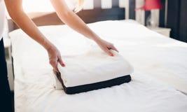 Hotelmädchen, das saubere frische Tücher auf Bett setzt stockbild