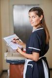Hotelowa gosposia z ilości listą kontrolną obrazy stock